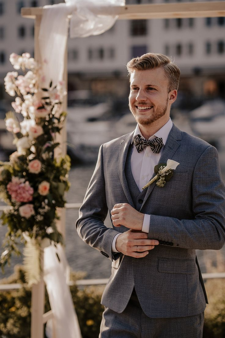 Blond groom with grey jacket. Black and gold bow tie.Wedding next to the water  ...
